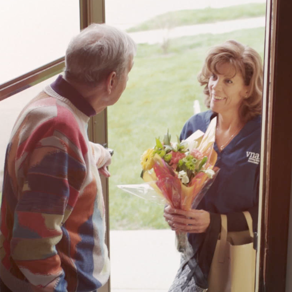 VNA caregiver at door with flowers