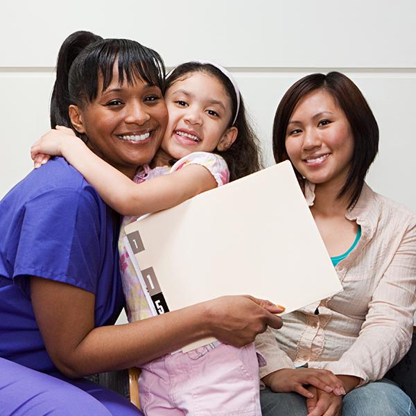 mother and child hugging caregiver