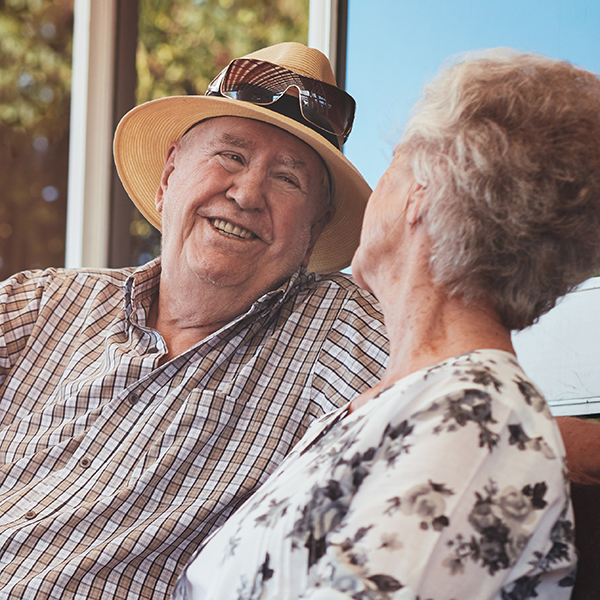 elderly couple smiling on bench