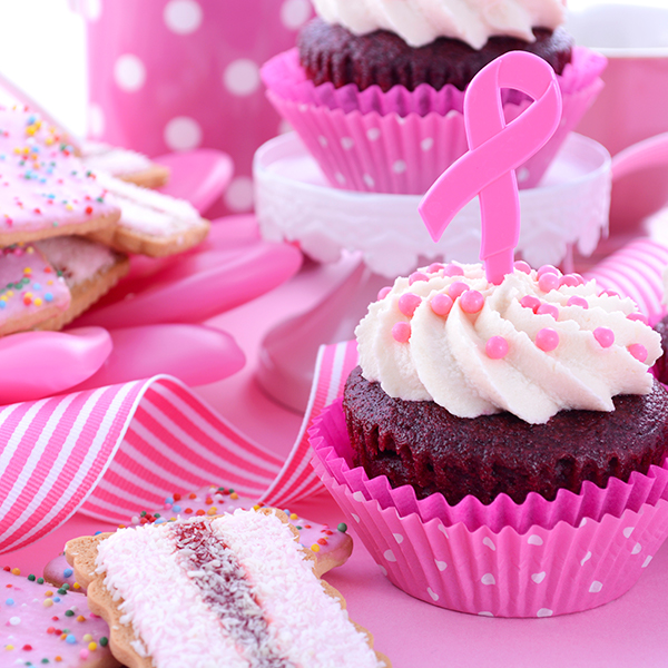 pink cupcakes with decorations and ribbon