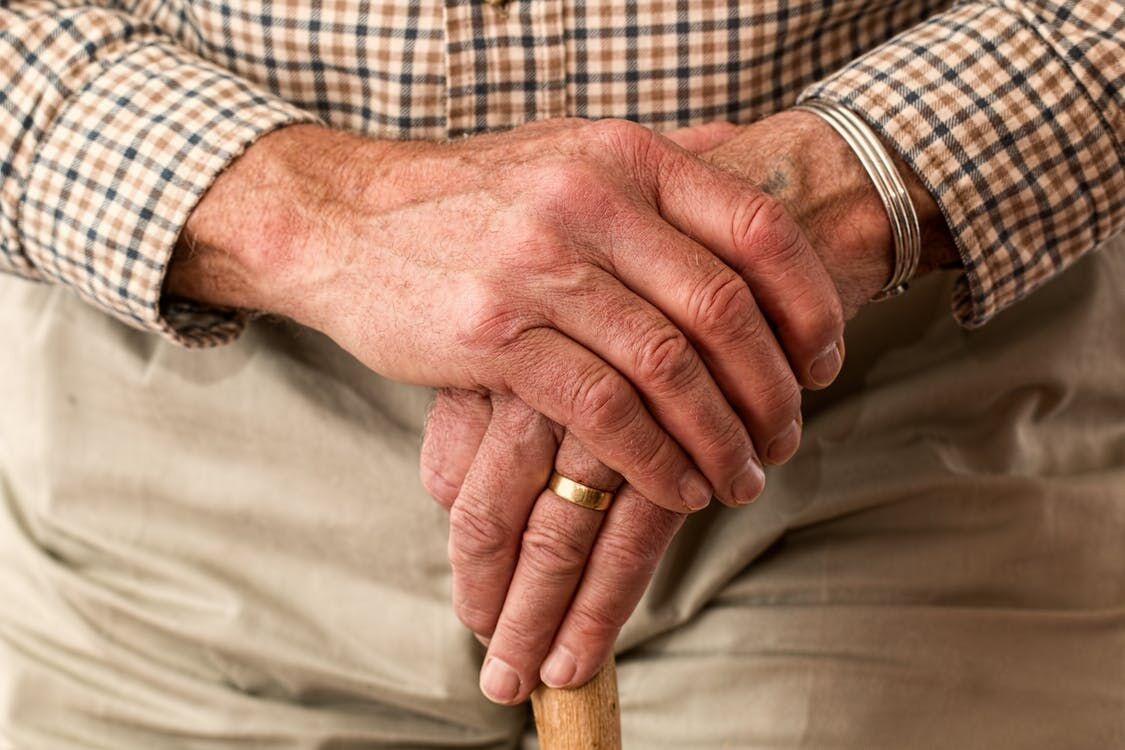 older gentleman with hands resting on top of cane