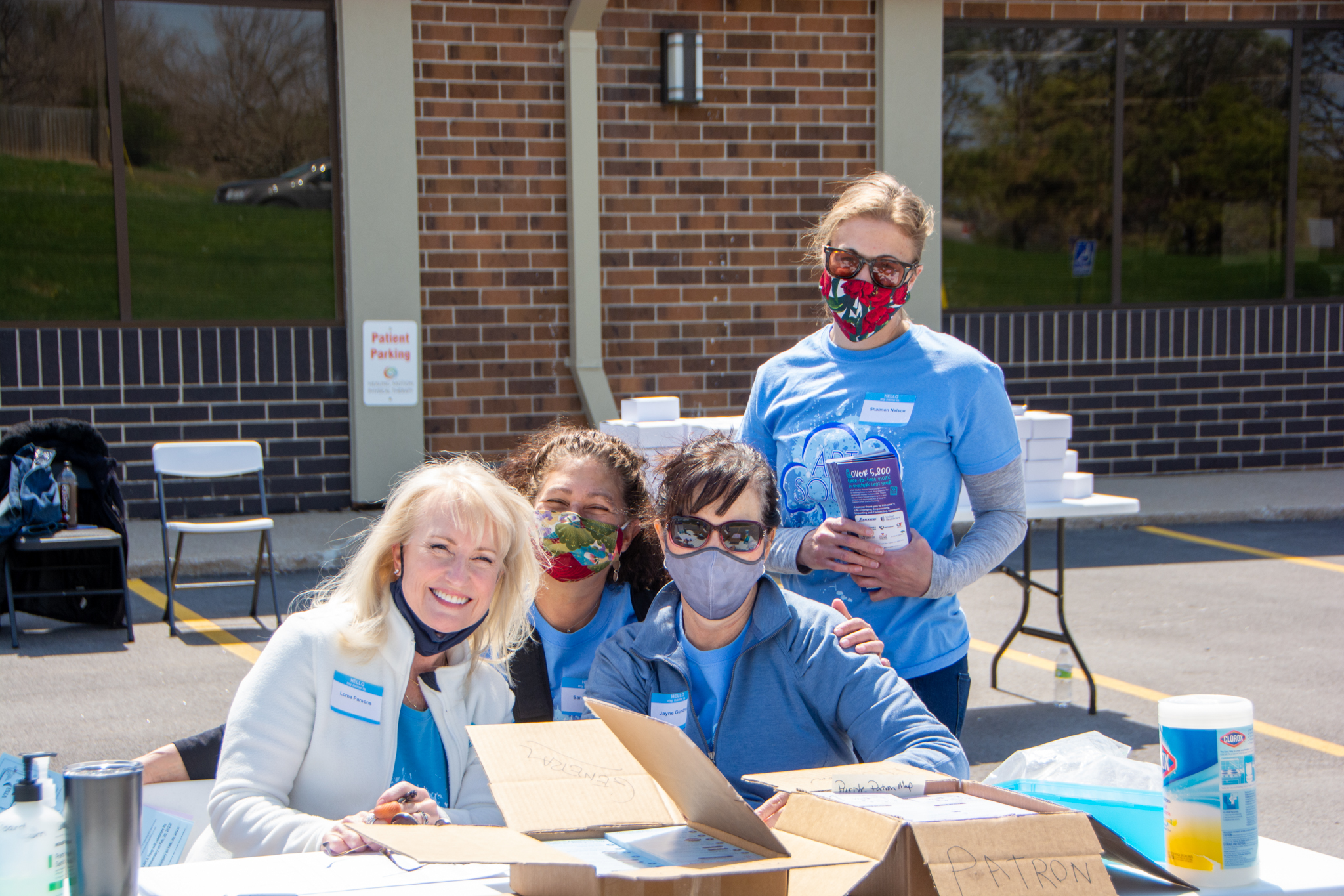 Art & Soup volunteers with masks at volunteer table outside of VNA's office